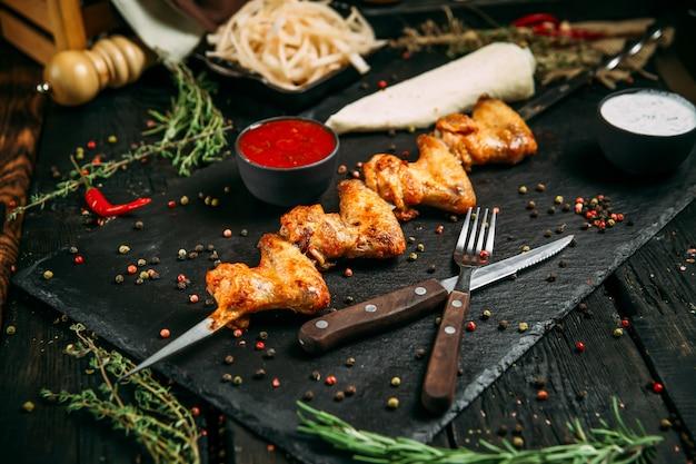 Bastone appetitoso di kebab delle ali di pollo su una superficie di legno nera