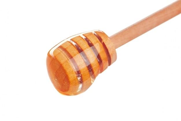 Bastone del miele con miele scorrente isolato su bianco
