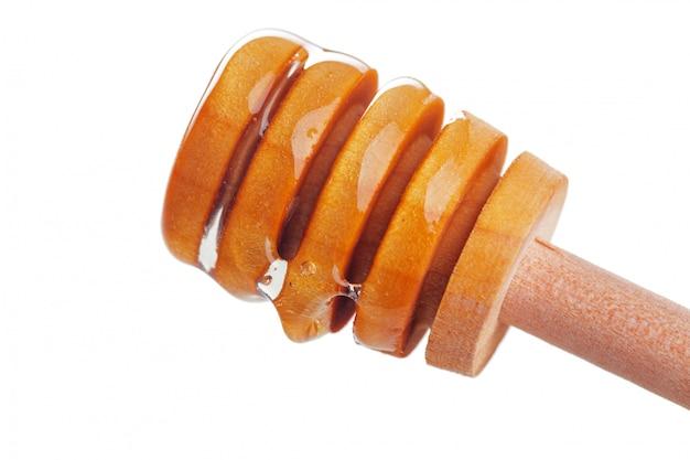 Bastone del miele con miele scorrente isolato