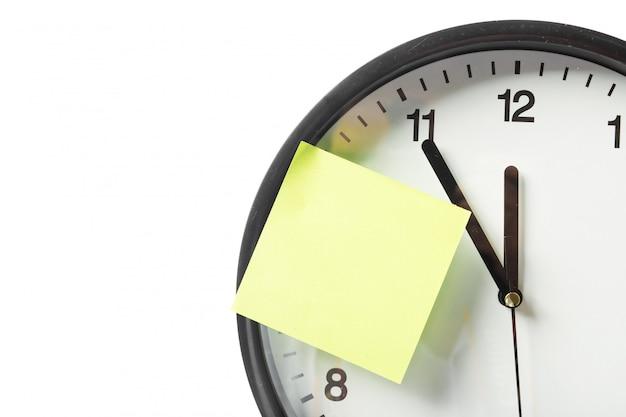 Bastone di carta sull'orologio per avviso qualcosa con sfondo bianco