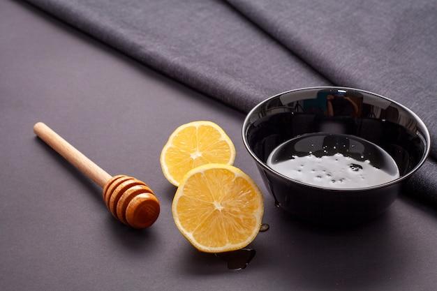 Bastone di miele del primo piano e fette del limone