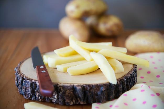Bastone di patate a fette pronto per fare patatine fritte - concetto di preparazione del cibo tradizionale
