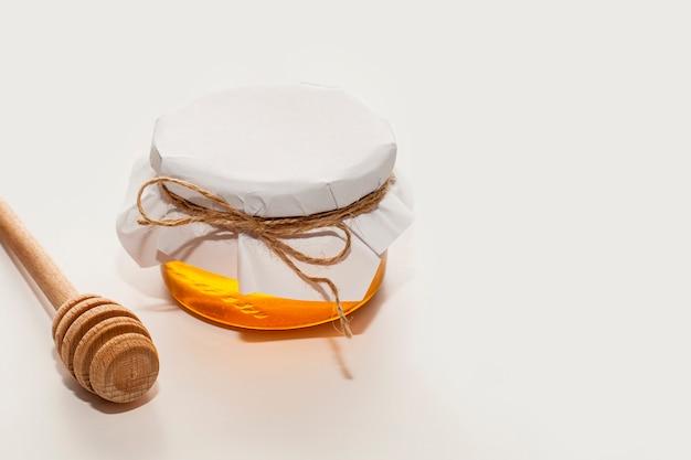 Bastone e barattolo di miele del primo piano su una tavola
