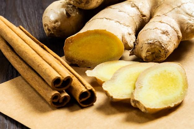 Bastoni di zenzero e cannella su fondo di legno scuro. additivi utili per il tè e bevande salutari