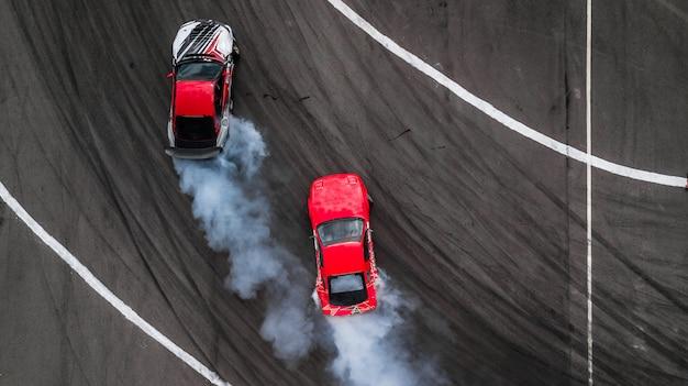 Battaglia di deriva aerea vista, due auto deriva battaglia su pista con fumo.
