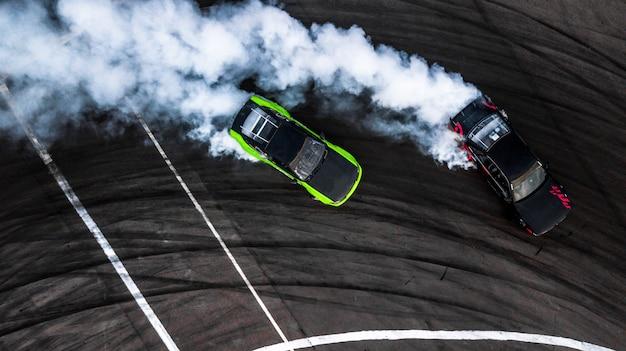 Battaglia di deriva auto, due auto alla deriva battaglia su pista con fumo, veduta aerea.
