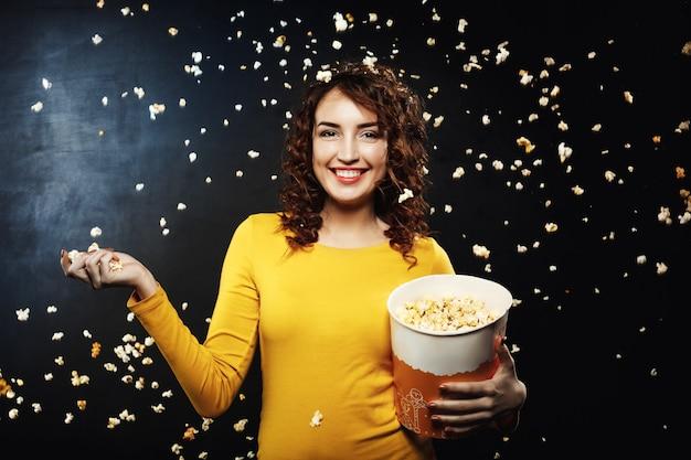 Battaglia di popcorn. gli amici che si divertono a casa fanno festa lanciando popcorn