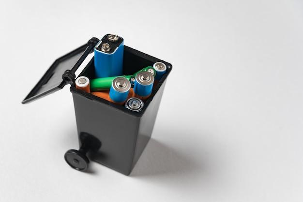 Batterie nel contenitore dell'immondizia su fondo bianco. concetto di riciclaggio della batteria. inquinamento ambientale con rifiuti domestici tossici.