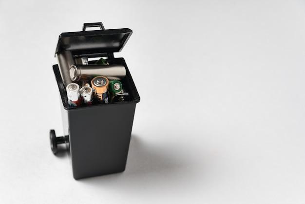 Batterie usate in contenitore dell'immondizia su fondo bianco. smaltimento corretto di batterie e accumulatori.