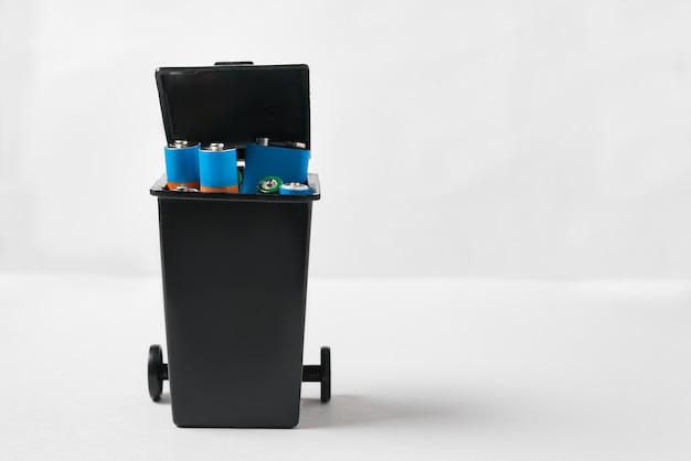 Batterie usate nel cestino. raccolta e riciclaggio del concetto di batterie usate. vista frontale