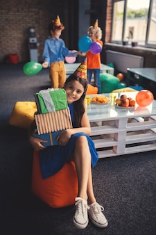 Bday. ragazza in un cappello che tiene i regali e che sembra soddisfatta