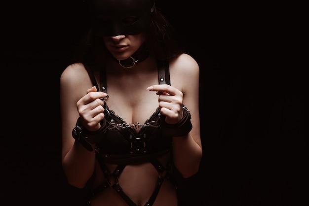 Bdsm. ragazza in manette e biancheria intima in pelle nera sexy da vicino