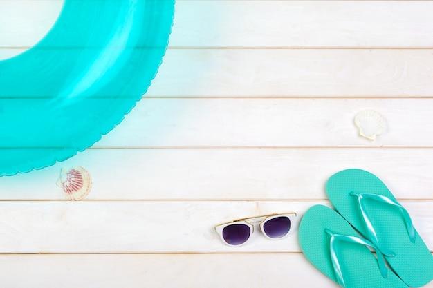 Beachwear e accessori su un fondo di legno bianco