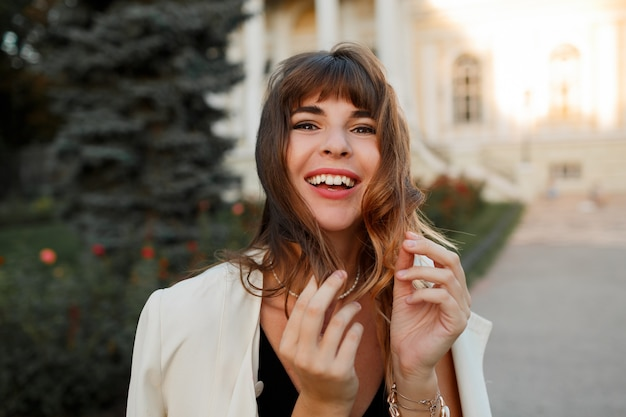 Beata donna che ride giocando con i capelli e godendo uotumn giorno in città europea. look elegante.