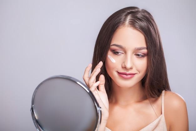 Beauty face, primo piano di sexy giovane donna con pennello correttore e specchio