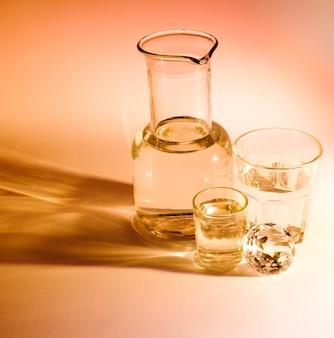Becher e due bicchieri d'acqua con ombra su sfondo colorato