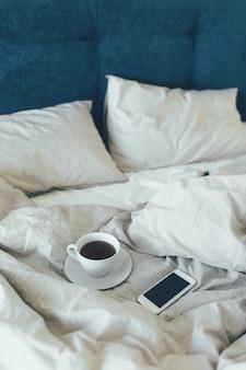 Bed-letto con cuscini e lenzuola bianche in sala bellezza. colazione del mattino con il tè