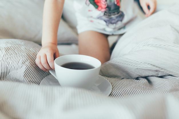 Bed-letto con cuscini e lenzuola pulite in camera. colazione del mattino con il tè kid hol