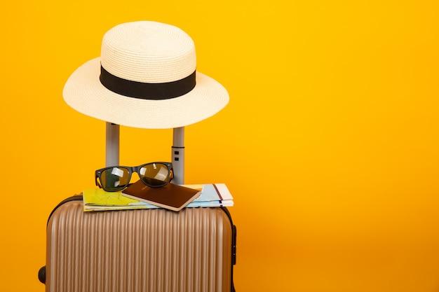 Bei bagagli e cappello isolati su fondo giallo, concetto accessorio di viaggio.