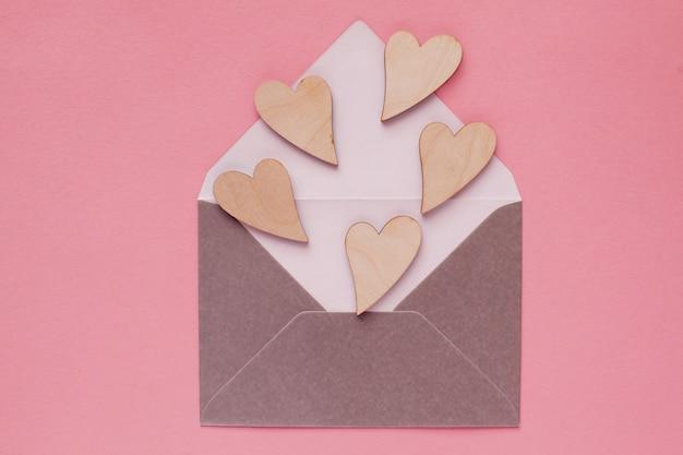 Bei cuori di legno in una busta di carta