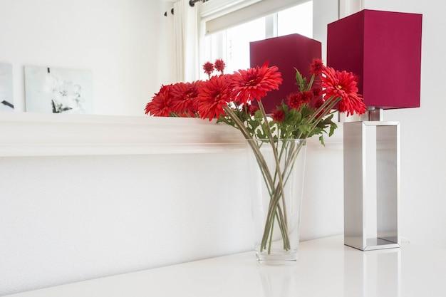 Bei fiori con la lampada da tavolo sul fondo bianco della parete con l'interno moderno del bello specchio