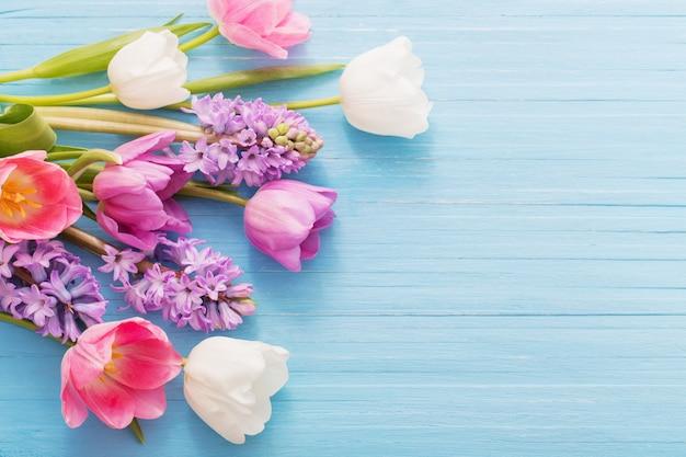 Bei fiori della molla su fondo di legno blu