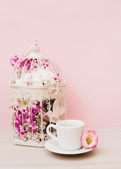 Bei fiori in gabbia bianca con la tazza e piattino sullo scrittorio di legno contro fondo rosa