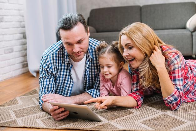 Bei genitori felici con la loro piccola figlia che per mezzo della compressa digitale