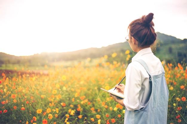 Bei giovani pantaloni a vita bassa che scrivono in un taccuino all'aperto in giardino floreale