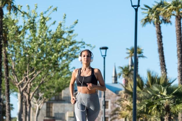 Bei giovani sport donna che esegue jogging in un parco all'aperto ascoltando musica