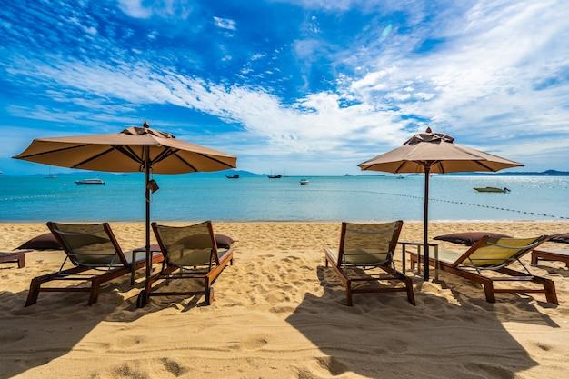 Bei mare ed oceano tropicali della spiaggia con l'albero del cocco ed ombrello e sedia su cielo blu