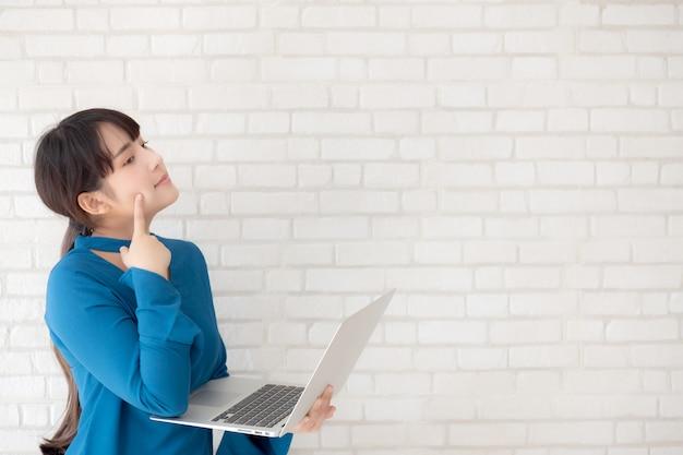 Bei pantaloni a vita bassa asiatici della giovane donna facendo uso dell'idea di pensiero del computer portatile funzionante