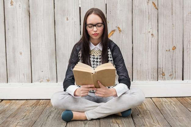 Bei pantaloni a vita bassa che leggono un libro