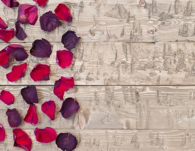 Bei petali di rosa su fondo rustico vintage. vecchie tavole di legno.