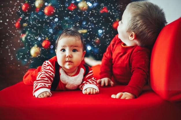 Bei piccoli cieli celebrano il natale. vacanze di capodanno i bambini in un costume di natale