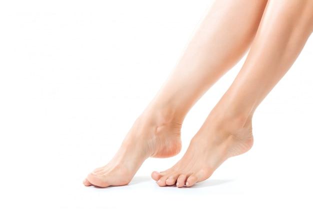 Bei piedi delle donne isolati sul primo piano bianco