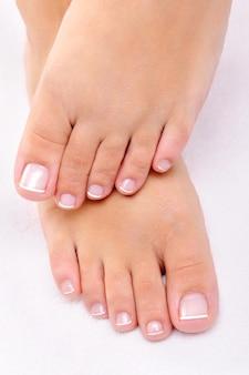 Bei piedi femminili con il pedicure francese su un asciugamano bianco
