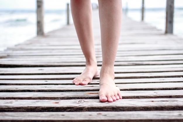Bei piedini e piedi della donna che camminano sul ponte di legno