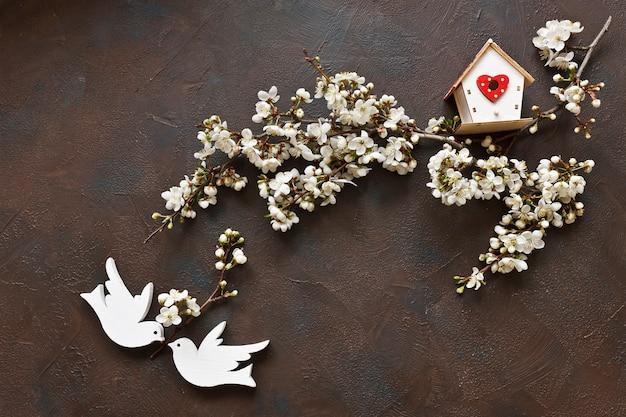 Bei rami di fioritura bianchi del ciliegio con due uccelli e birdhouse di legno.