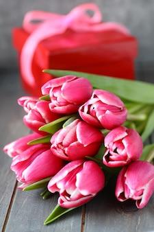 Bei tulipani rosa con il contenitore di regalo su fondo di legno