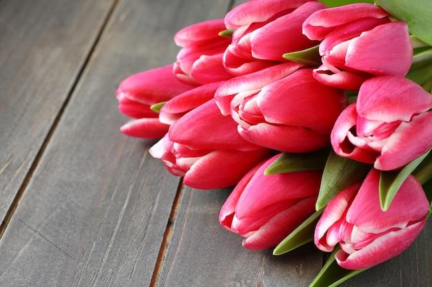 Bei tulipani rosa su fondo in legno