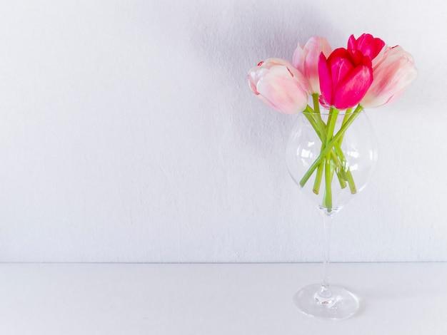 Bei tulipani vivi in vetro su fondo bianco.