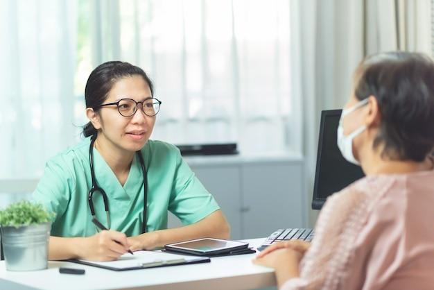 Bei vetri asiatici di usura di medico della donna che parlano e che danno consiglio alla paziente anziana della donna nella stanza medica all'ospedale.