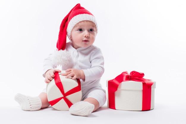 Bel bambino seduto in un cappello di capodanno e corpo bianco