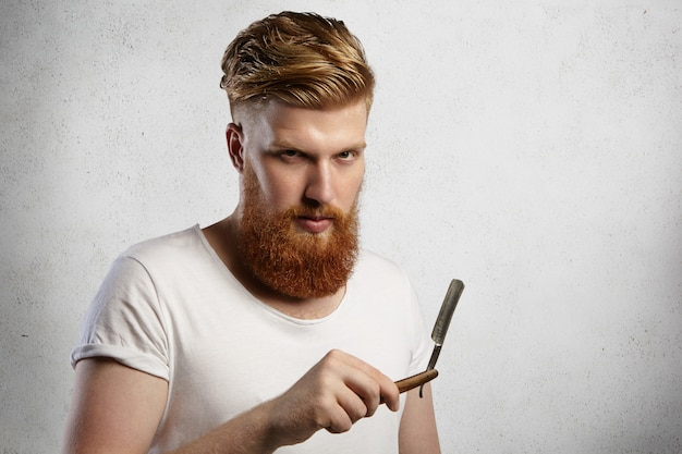 Bel barbiere con folta barba che tiene il suo accessorio da barbiere, dimostrando affilata lama di rasoio a mano libera.