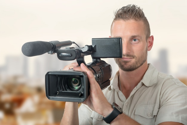 Bel cameraman con videocamera professionale