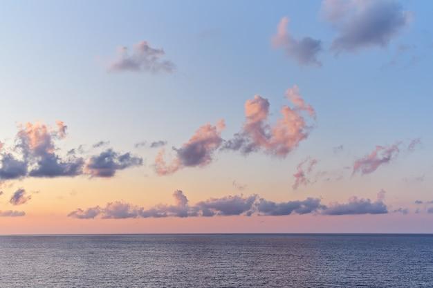 Bel cielo al tramonto con cumuli sopra la superficie del mare con luce drammatica