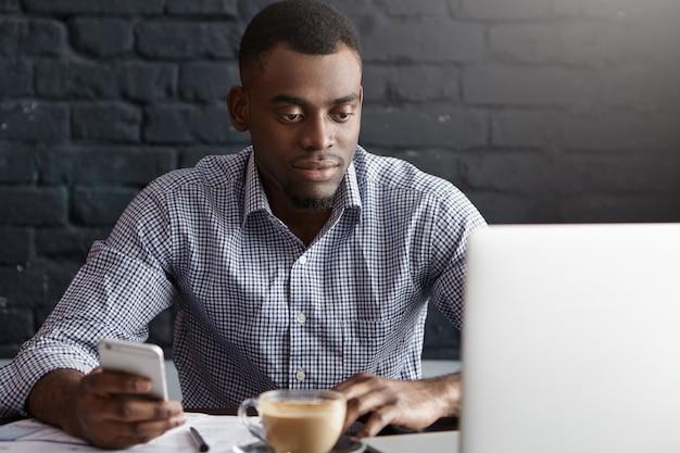 Bel giovane africano in camicia formale, navigare in internet sul telefono cellulare
