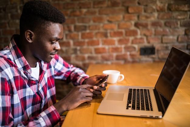Bel giovane afroamericano sorridente felicemente durante la lettura di sms su smart phone, messaggistica utilizzando la connessione wi-fi gratuita, un caffè al bar