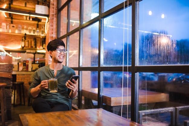 Bel giovane asiatico lavora su laptop, guarda video su smartphone, tiene telefoni cellulari e naviga sul web usando il 5g ad alta velocità.